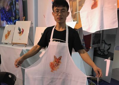 Boy wearing white apron with orange fox watercolour by Joan Kennedy Artist